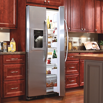 A refrigerator with an open door in a kitchen.