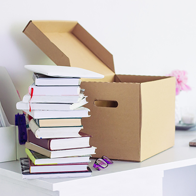 A stack of books next to a cardboard box.