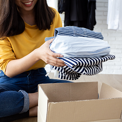 Woman placing folded shirts into a moving box.
