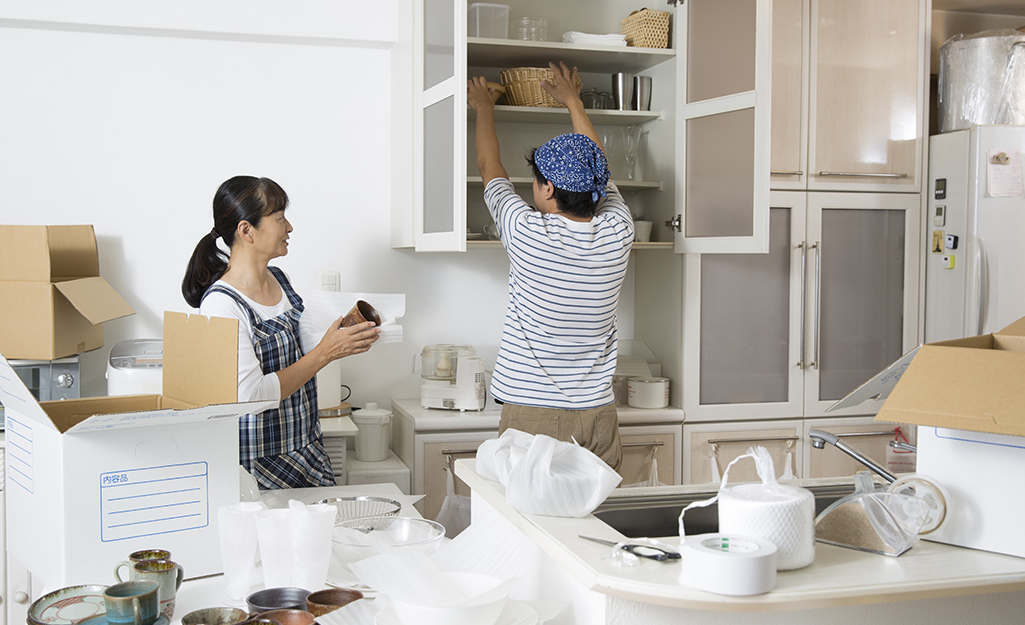 Couple packing up dishes in the kitchen..