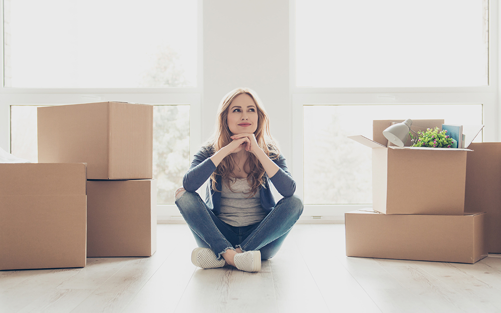 Woman sitting in room with packed boxes.