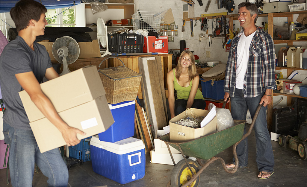 Three people cleaning and packing a garage.
