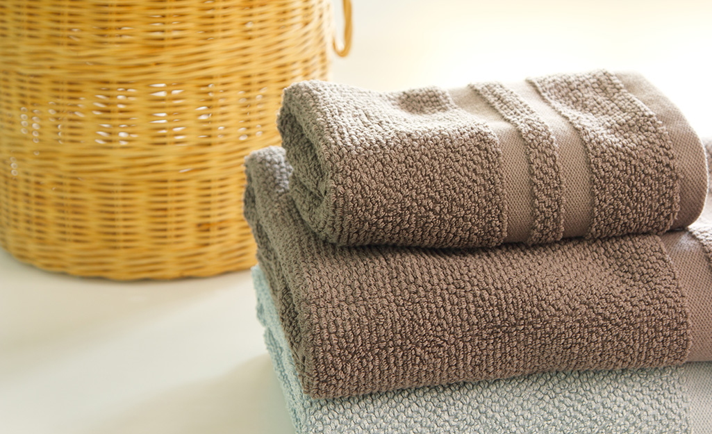Two towels stacked next to a woven wicker basket.