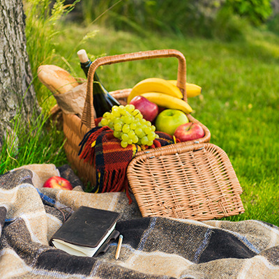 A picnic basket full of fruit and bread sits on a blanket outdoors.