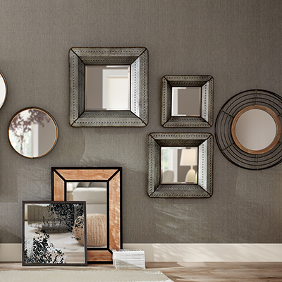 Mirrors of different sizes and shapes hanging on a wall.