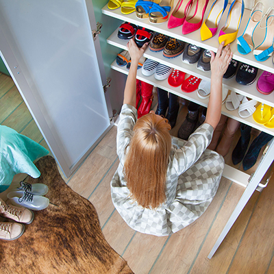 Woman organizing shoes in her closet.