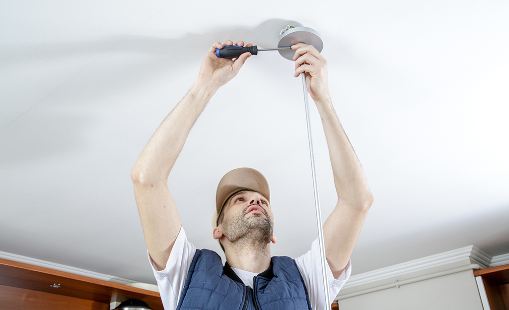 A person removes a fixture from a ceiling.