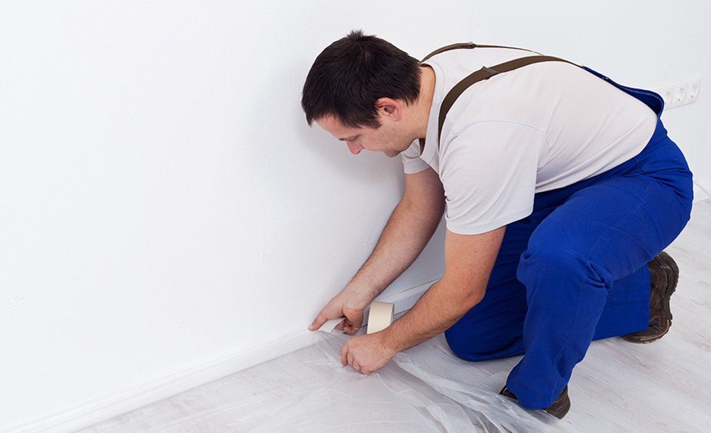 A man secures a drop cloth to the floor to prevent damage from ceiling paint.