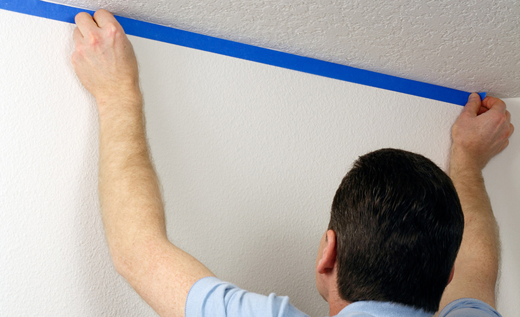A Man Uses Painter S Tape To Prep The Walls Before Painting Ceiling