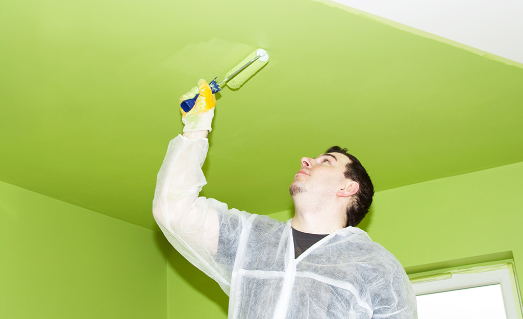 A person paints a ceiling with a roller.