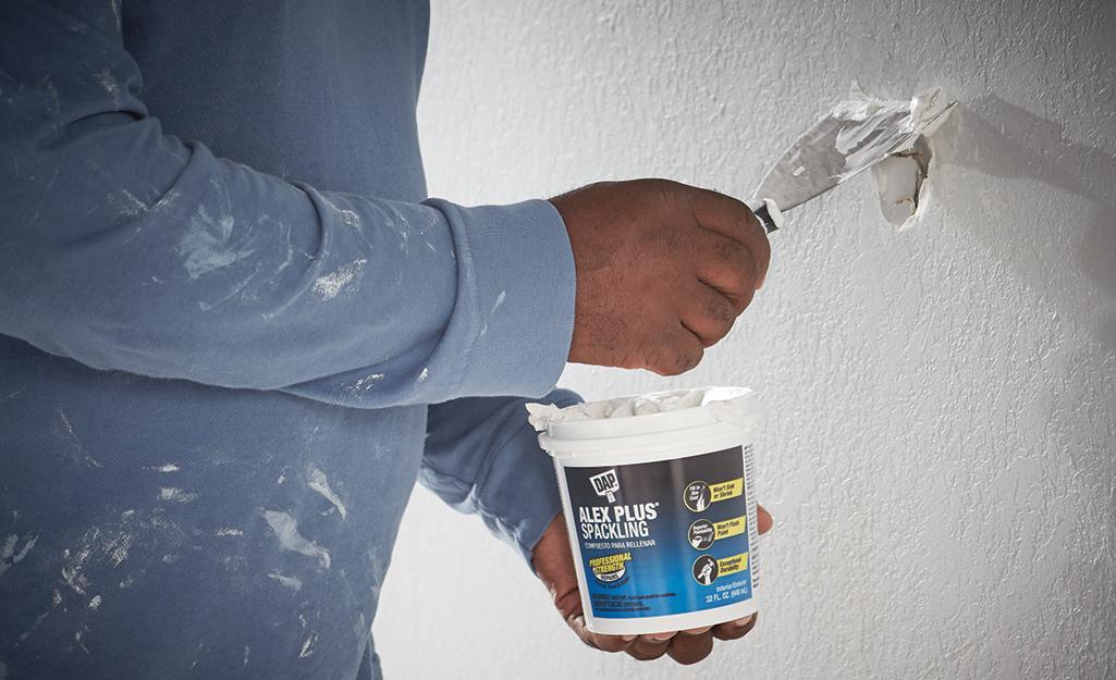 Một người áp dụng hợp chất rải rác lên tường.