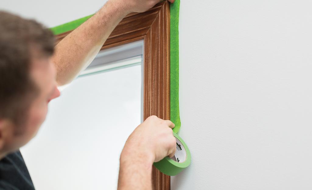 Một người dán băng dính của họa sĩ xung quanh khung cửa.