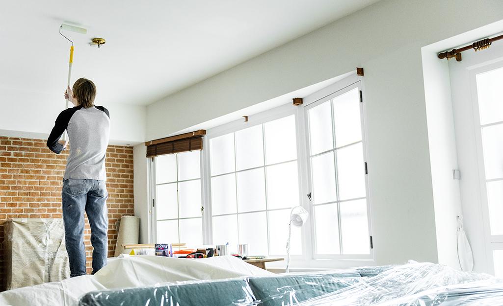 Một người sử dụng con lăn sơn có phần mở rộng để sơn trần nhà.