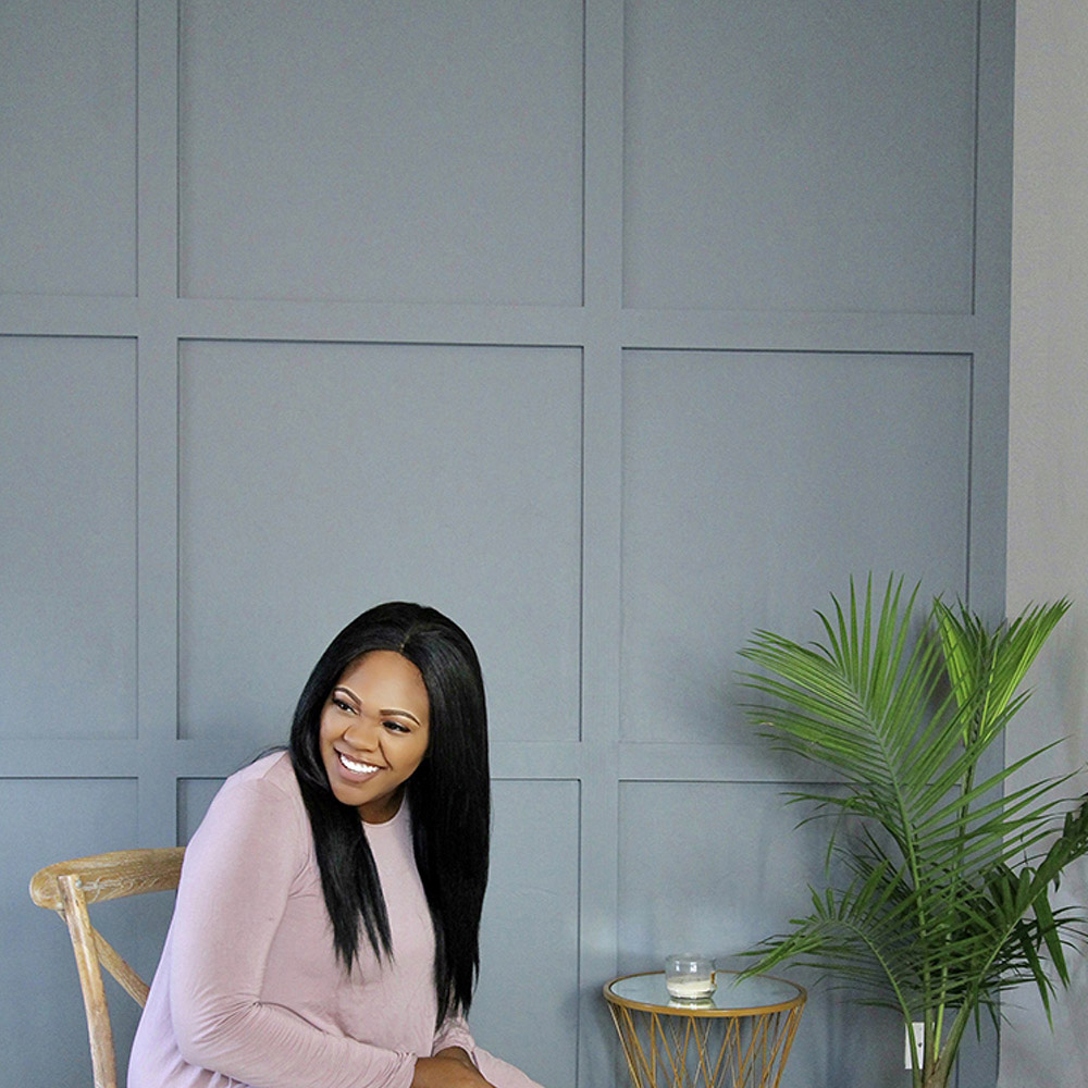 A woman sitting in front of a painted accent wall.