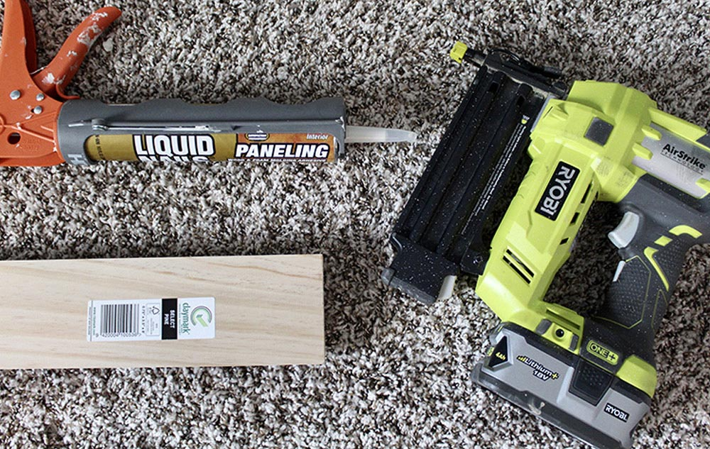 Various tools and materials needed to add paneling to a wall.