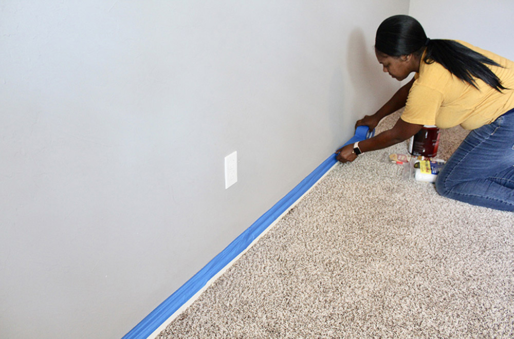 A woman taping the edges of a baseboard with painter's tape.