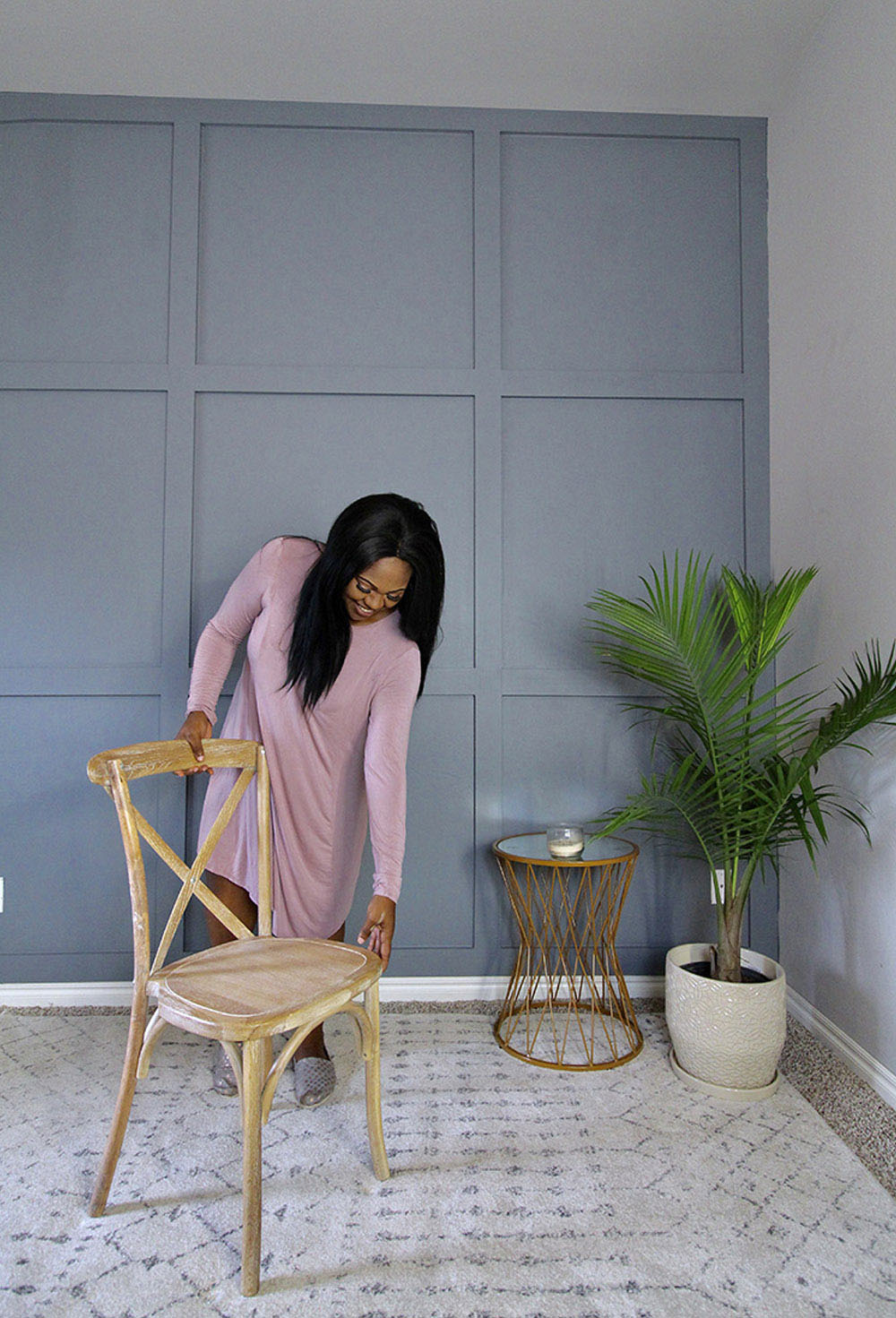 A woman moves a chair on a rug.
