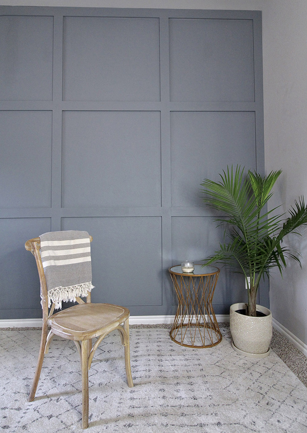 A room decorated with a chair, table, and greenery in front of a painted accent wall.