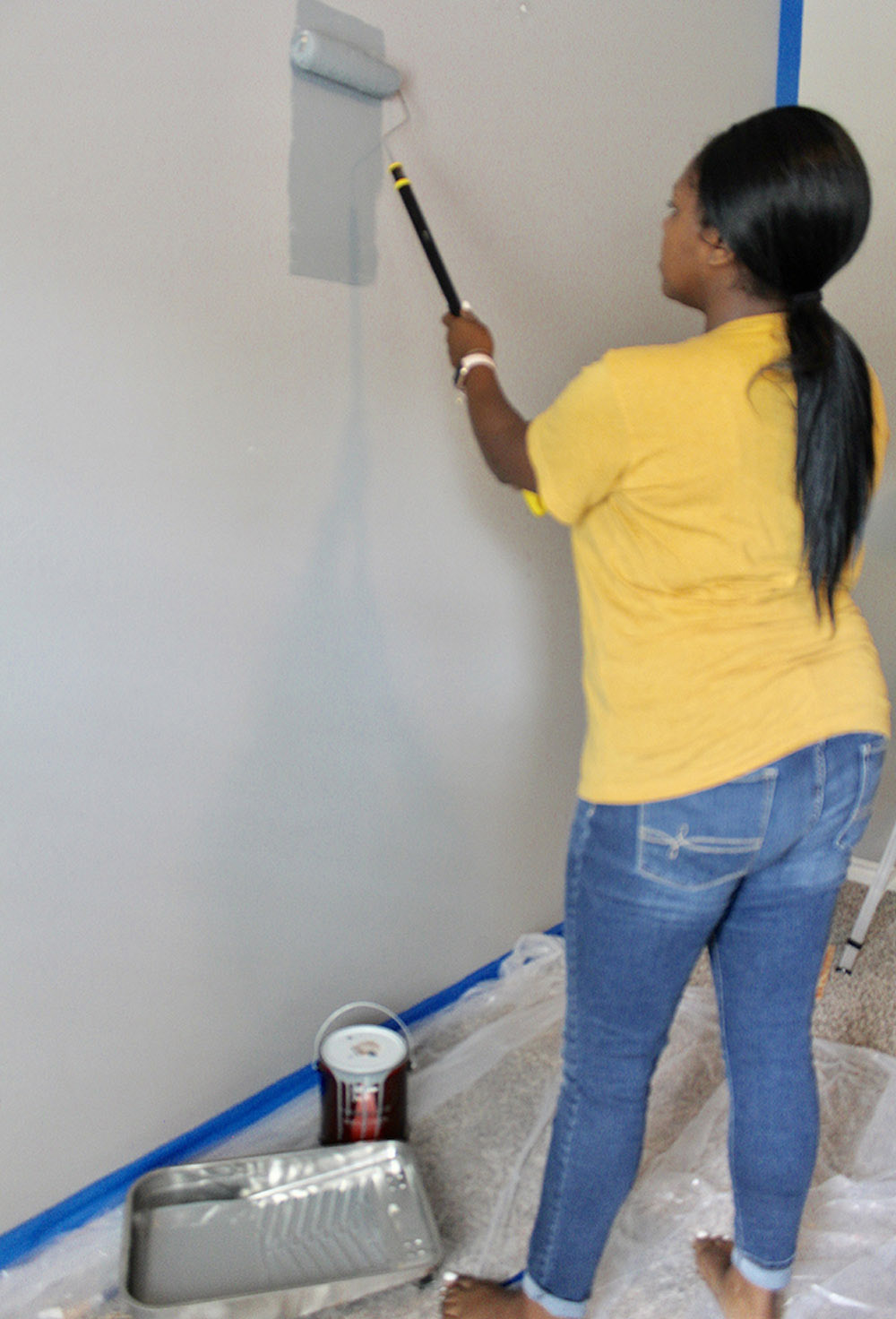 A woman rolling paint onto a wall.