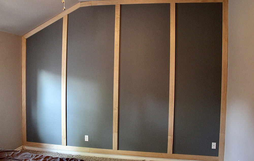 A painted accent wall with vertical pieces of trim attached.