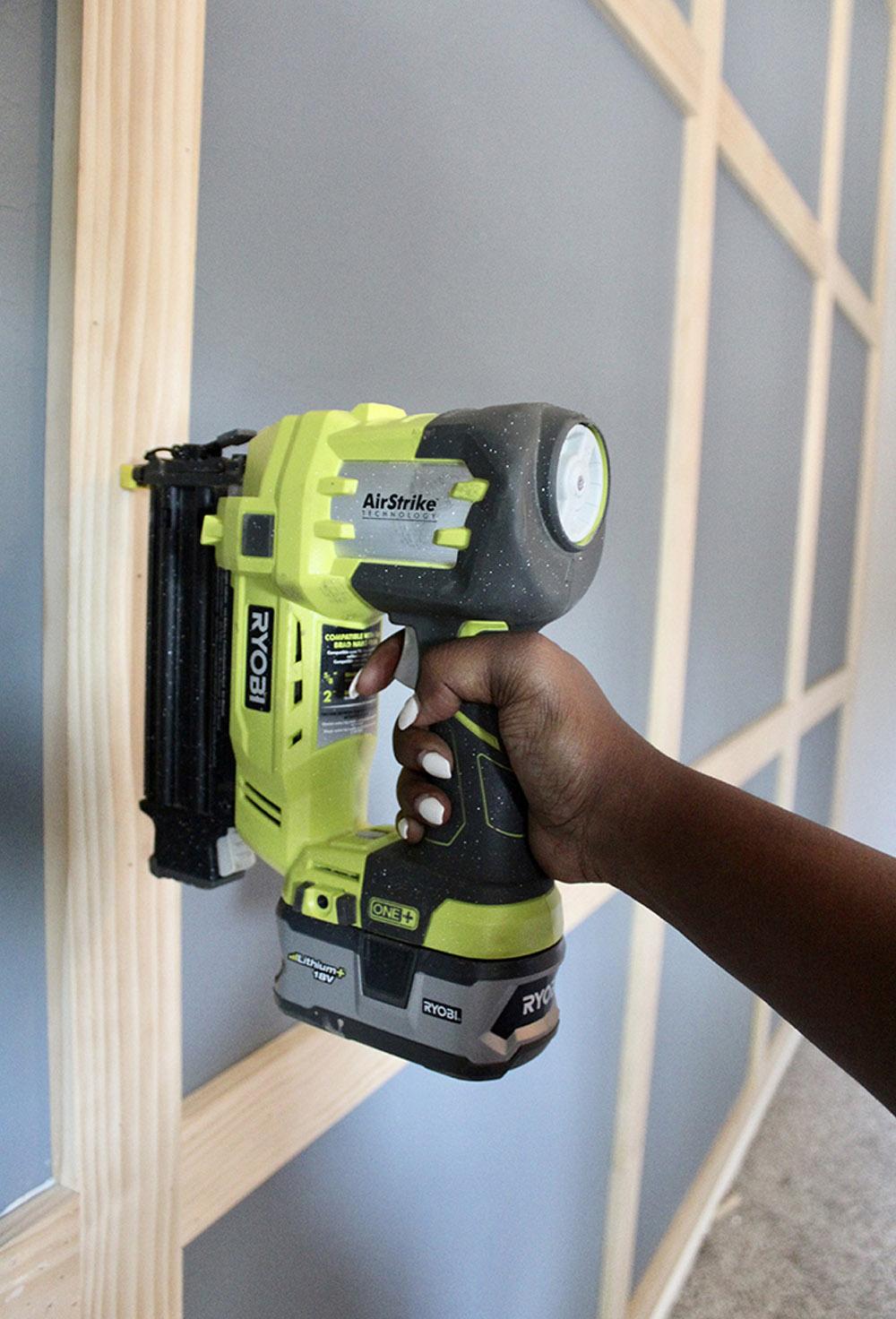 A person using a nail gun to attach trim to a wall.