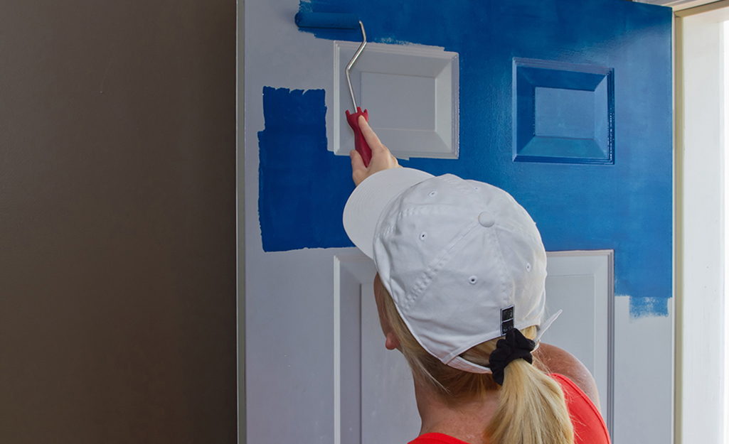 A woman rolling blue paint onto a door.