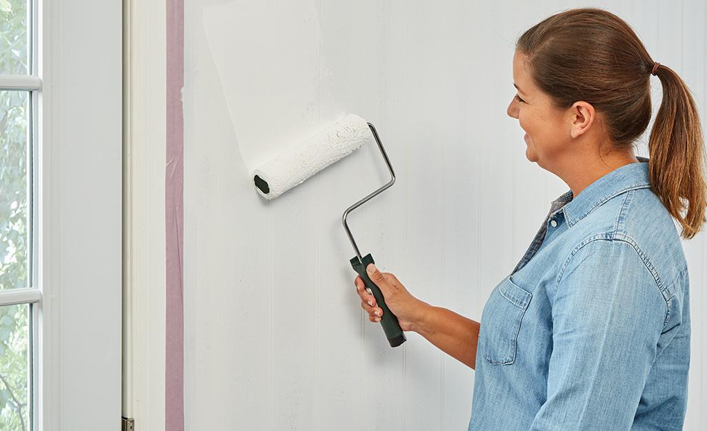 Người phụ nữ sơn tấm ván trắng bằng con lăn.