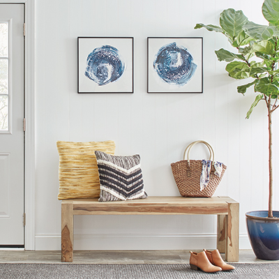 A entryway bench in front of a painted, paneled wall.