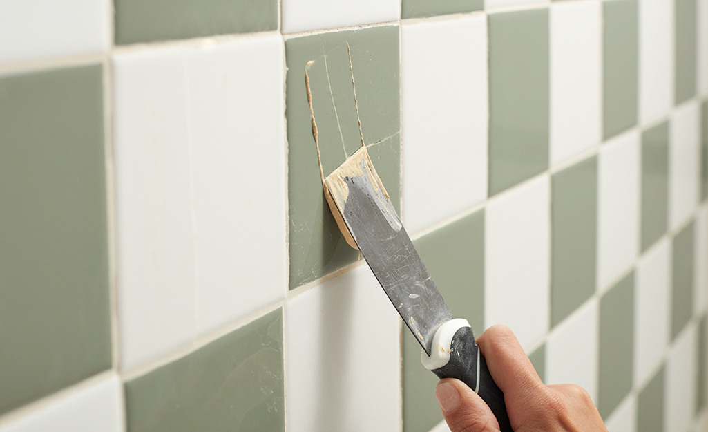 Someone patching green and white checkerboard tile.