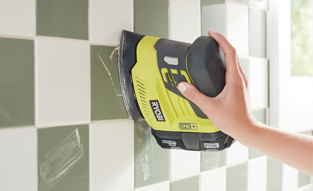 Someone sanding green and white checkerboard tile.
