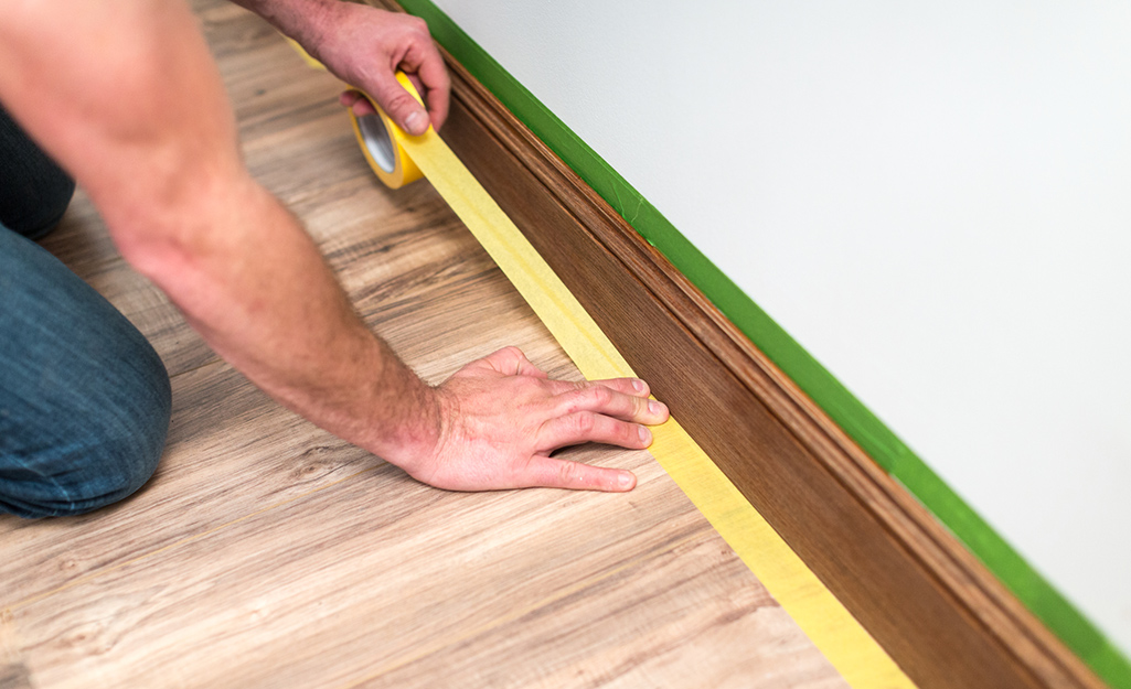 A person applying painter's tape to the floor along the baseboard.