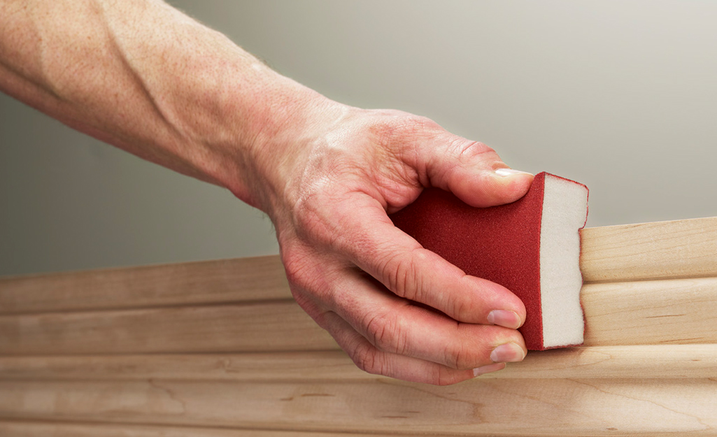 A person using a sanding sponge on wooden trim.