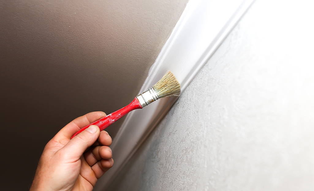 A person using a paint brush on crown moulding.