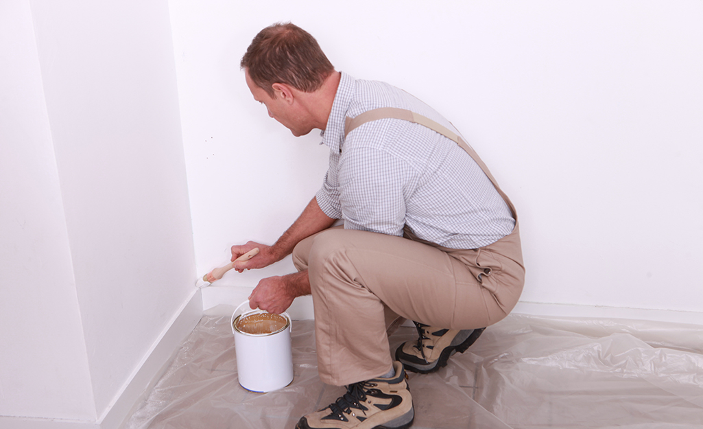 A person using a paint brush to paint the baseboard in the corner of a room.