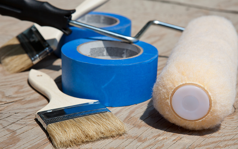 Painter's tape, brush and roller laying on a table