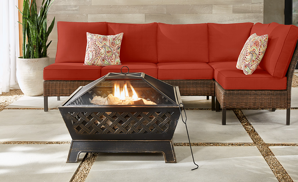 A metal fire pit and outdoor furniture on a patio.