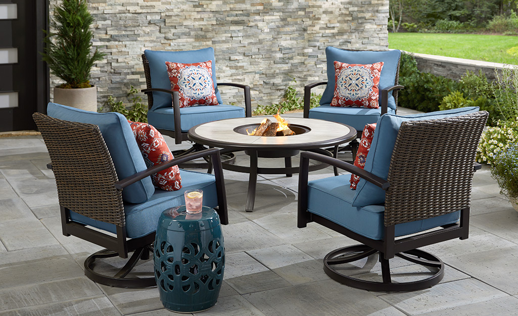 A round fire pit table and chairs on a patio.