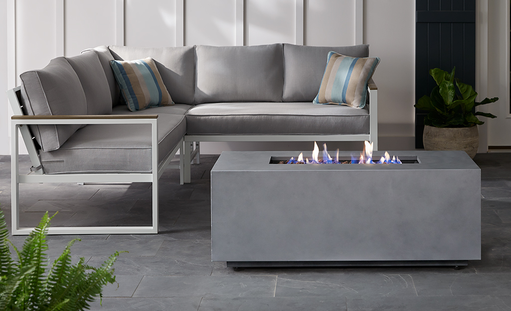 A rectangular fire pit and outdoor sectional on a patio.