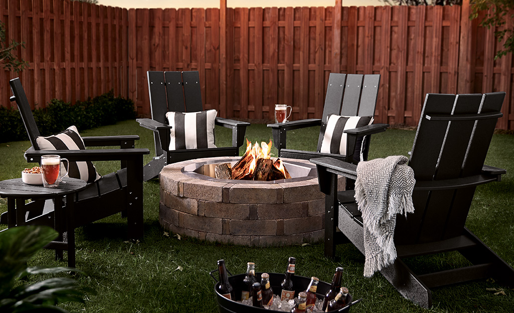 A brick fire pit with Adirondack chairs in a backyard.