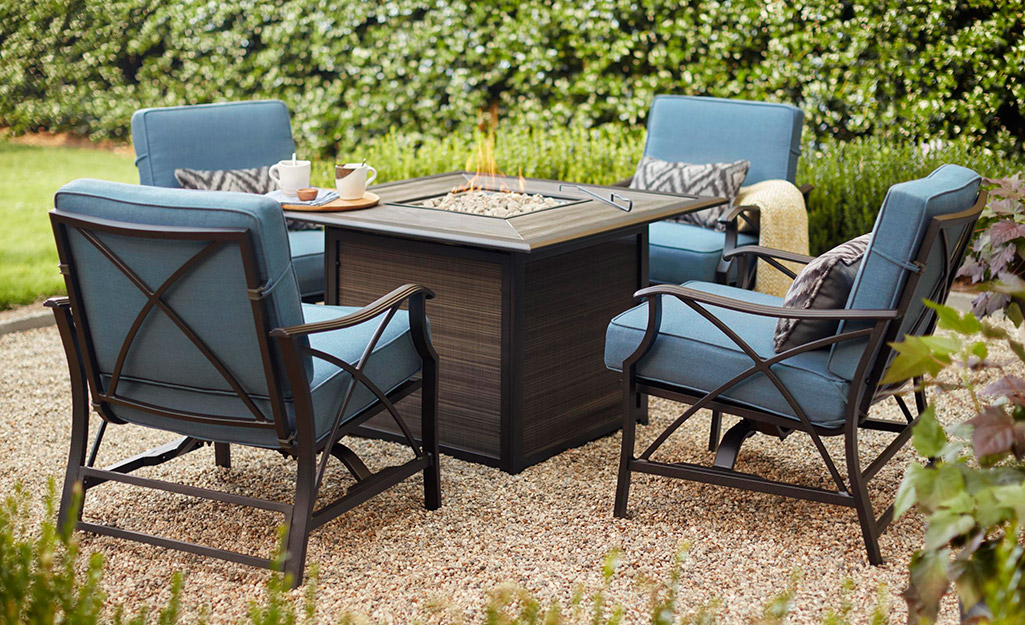 A square fire pit table and chairs on a patio.