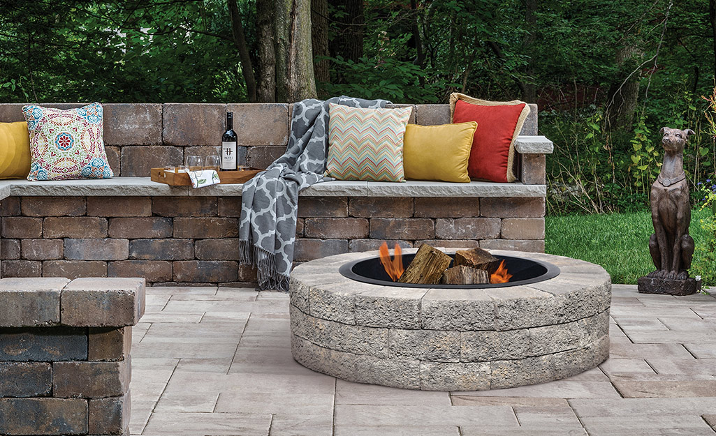 A stone fire pit and stone bench on a patio.