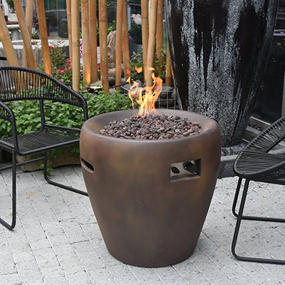 A gas fire pit with two chairs on a patio.