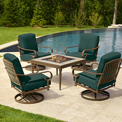 Patio set with a fire pit and four armchairs beside a pool.