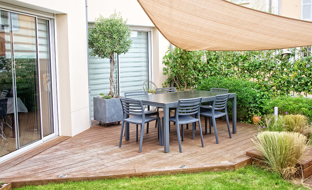 A small, asymmetrical wood deck with a canopy and outdoor dining table.