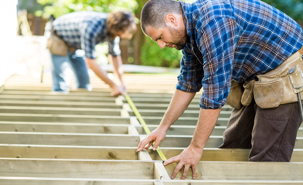 Two people measuring and constructing deck joists.