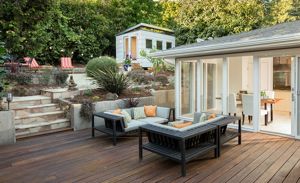 A furnished outdoor entertainment space that blends together a wood deck, stone patio and elevated garden beds.