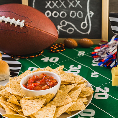 Chips and salsa sit on a table near playoff party decorations.