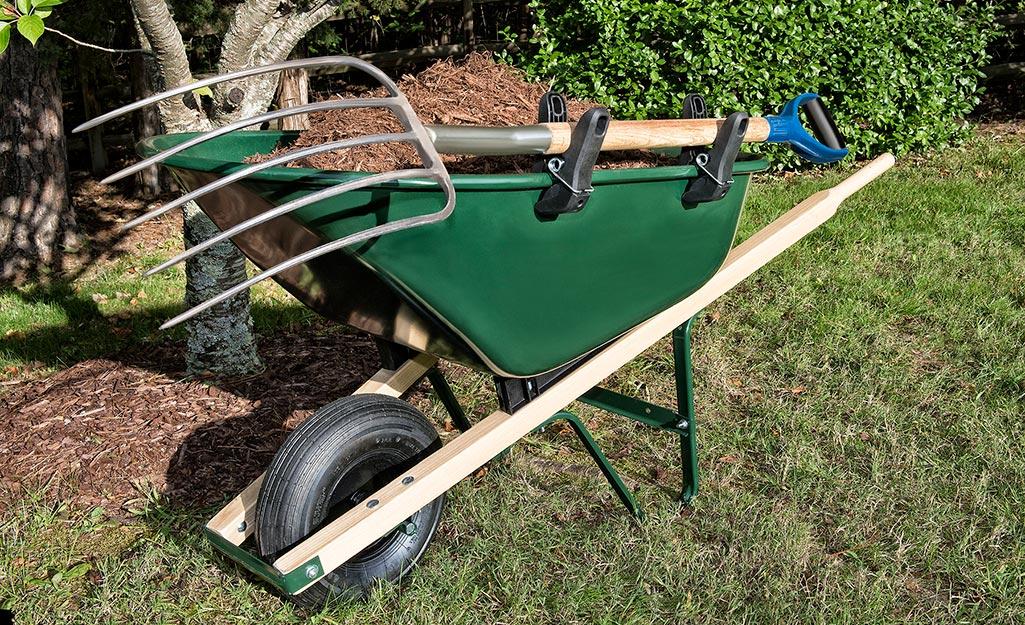 A pitchfork laying atop a wheelbarrow.
