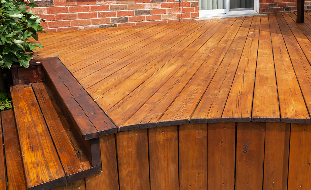 A newly stained  wood deck next to a brick house.