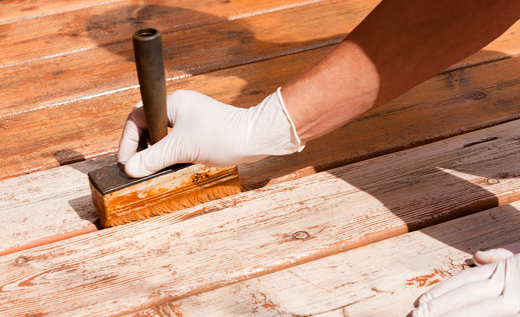 A person running a paintbrush between two deck boards.